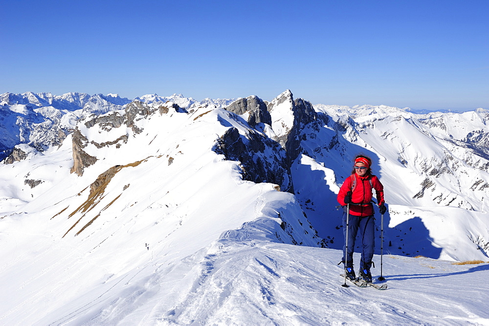 Woman with crosscountry skis ascending to Rofanspitze, Seekarlspitze, Hochiss and Karwendel range in the background, Rofanspitze, Rofan, Tyrol, Austria, Europe