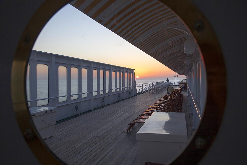 Sunset view through window on deck of cruise ship MS Deutschland (Reederei Peter Deilmann), Caribbean Sea, near Mexico