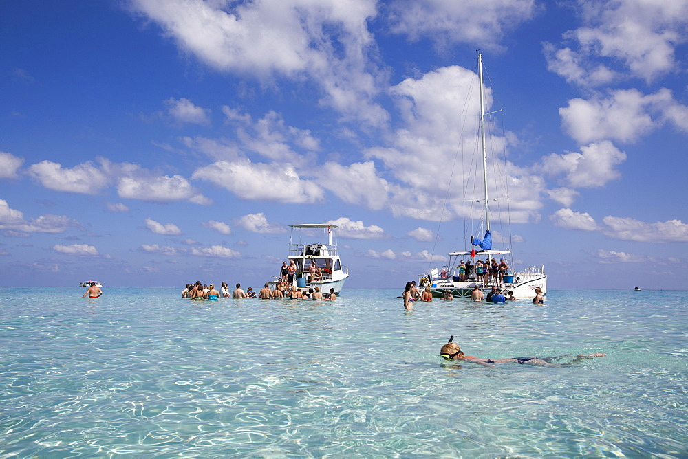 Snorkeler and excursion boats at Stingray City sand bank, Grand Cayman, Cayman Islands, Caribbean