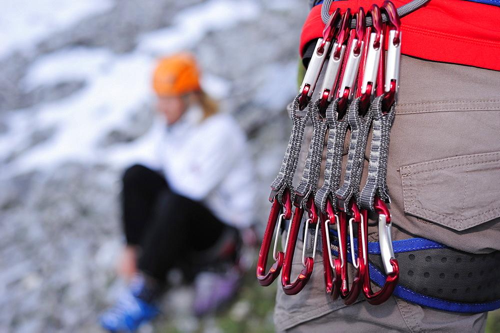 Runners hanging from climbing harness, Multerkarwand, Treffauer, Wegscheidalm, Wilder Kaiser, Kaiser Mountain Range, Tyrol, Austria