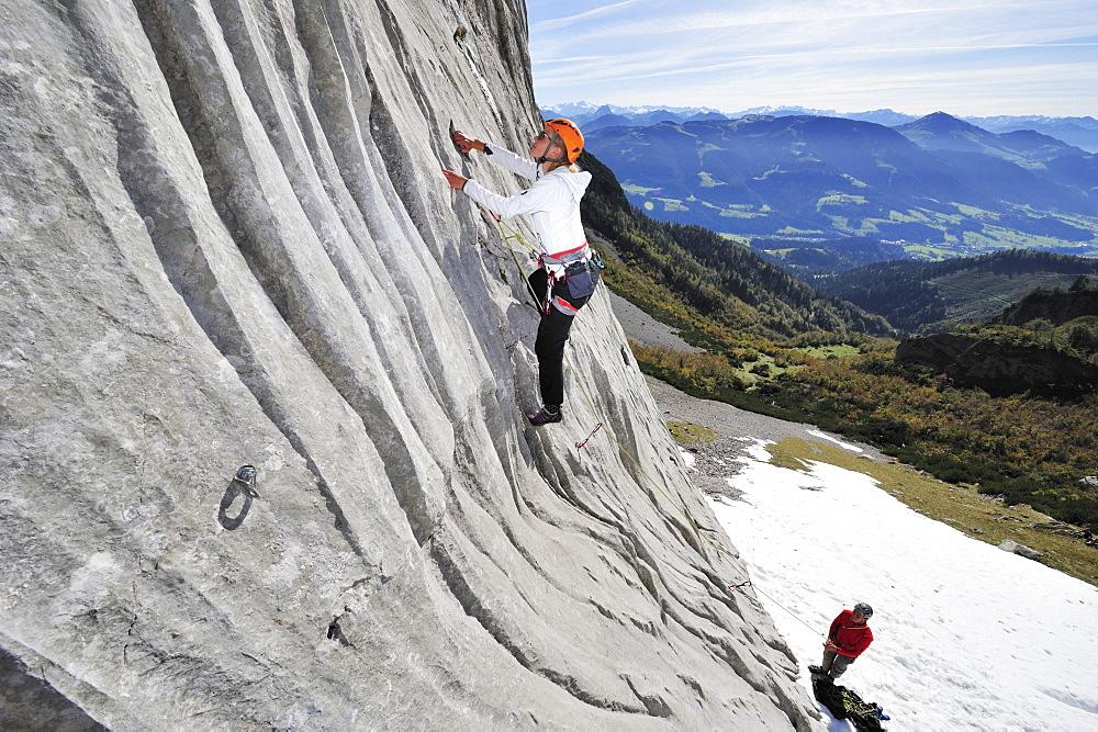 Young woman climbing while young man belaying, Multerkarwand, Treffauer, Wegscheidalm, Wilder Kaiser, Kaiser Mountain Range, Tyrol, Austria