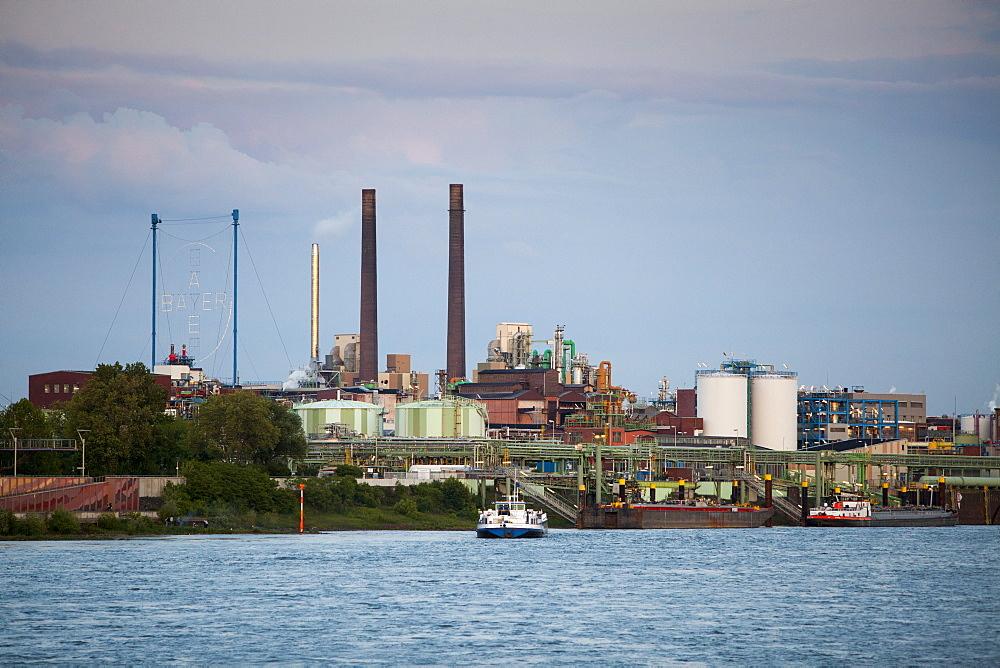 Rhine river and Bayer chemical and pharmaceutical company factory chimneys at dusk, Leverkusen, North Rhine-Westphalia, Germany, Europe