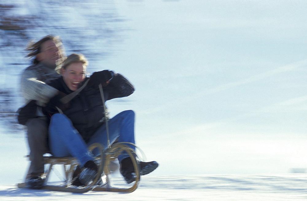 Couple sledding downhill