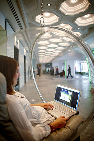 Woman sitting in a hanging ball chair while using a laptop, hotel lobby, Brussels, Belgium