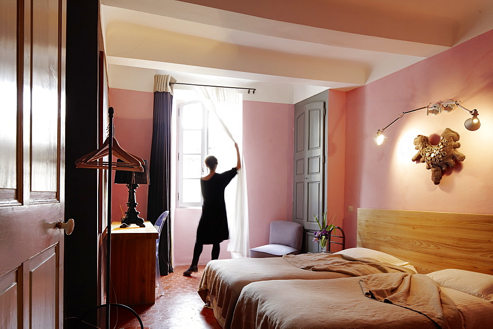 Woman opening curtains, Bedroom with double bed, B and B Chambre Avec Vue, Luberon, France