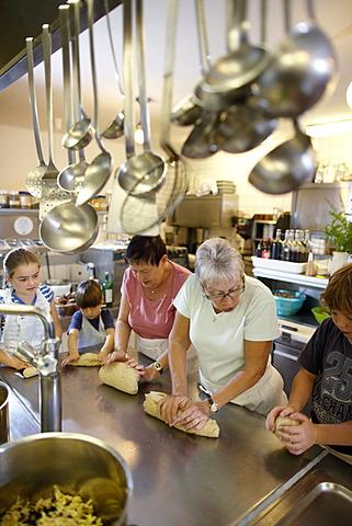 Women and children baking in a hotel kitchen, Am Hochpillberg, Schwaz, Tyrol, Austria