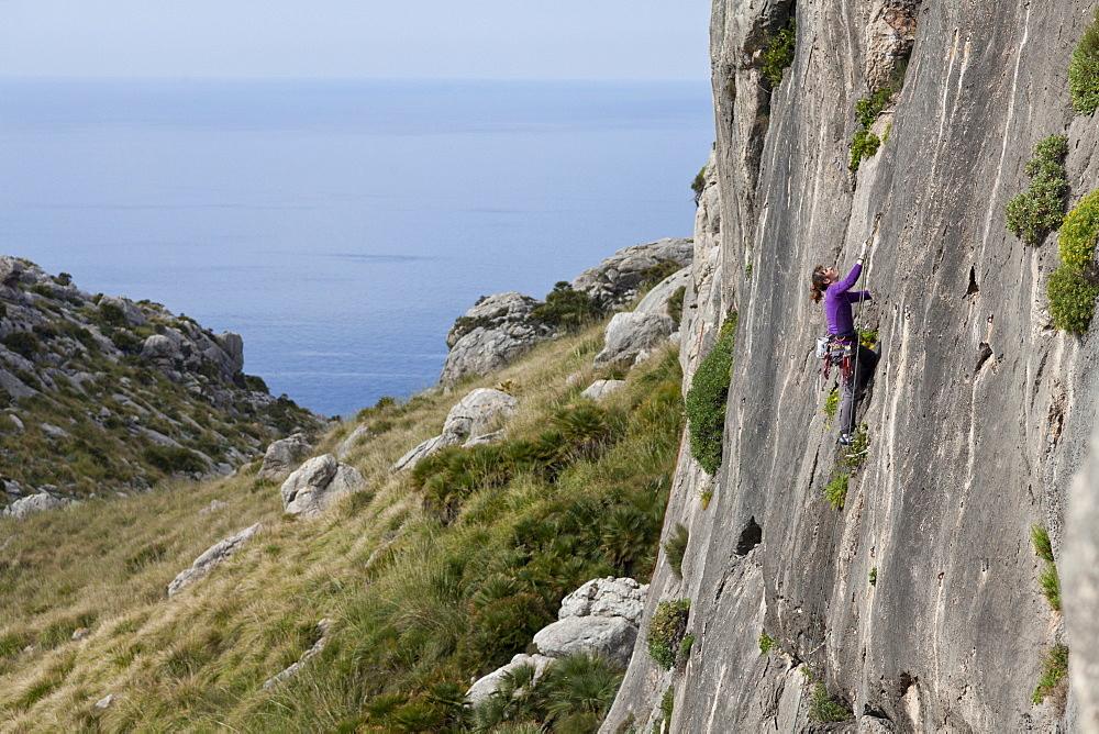 Young women climbing in a steep wall, hiking and climbing on Mallorca, climbing area La Creveta, Cap Formentor, Mediterranean Sea, La Creveta, Cap de Formentor, Serra de Tramuntana, Unesco World Cultural Heritage, Mallorca, Spain