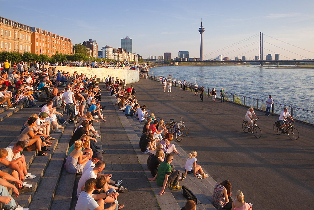People sitting on the stairs to the Rhine river promenade, Duesseldorf, North Rhine-Westphalia, Germany, Europe
