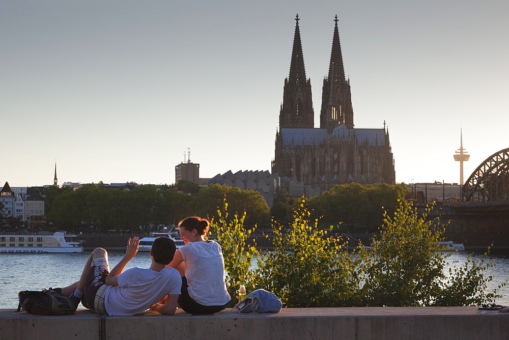 Young couple sitting on the Rhine river banks opposite to the cathedral, Cologne, North Rhine-Westphalia, Germany, Europe