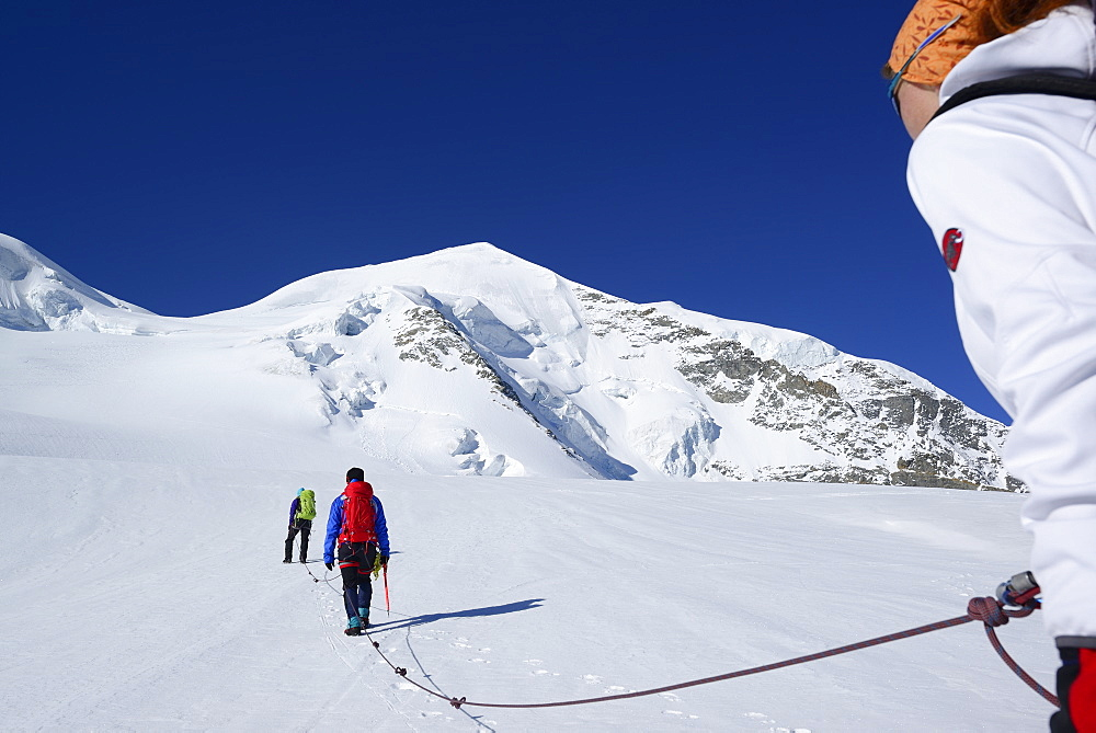 Three mountaineers ascending to Piz Palue, Grisons, Switzerland
