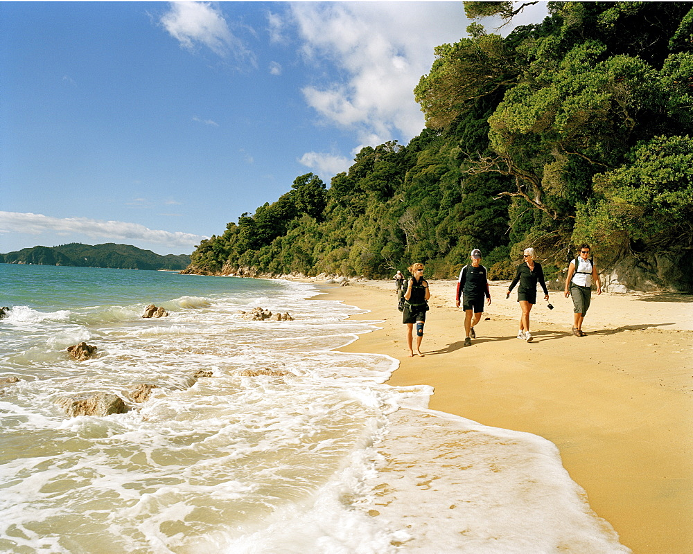 Hikers on Waiharakeke Beach in the sunlight, Abel Tasman National Park, North Coast, South Island, New Zealand