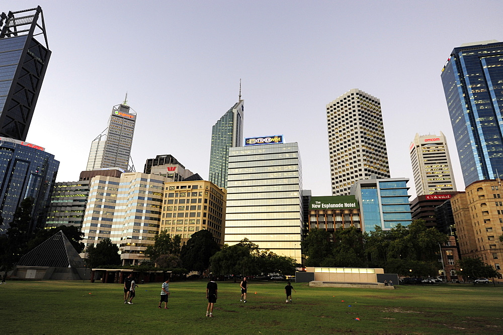 People playing football at dusk, Esplanade, skyline of the business district, Central City Area, Perth, Western Australia, WA, Australia