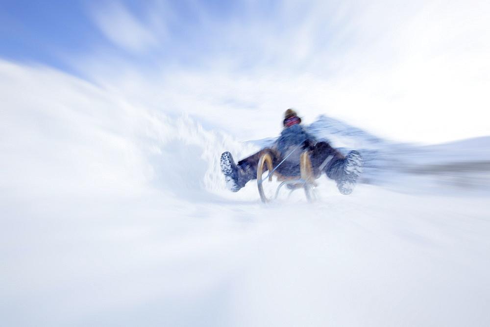 Woman sledding, Kuehtai, Tyrol, Austria