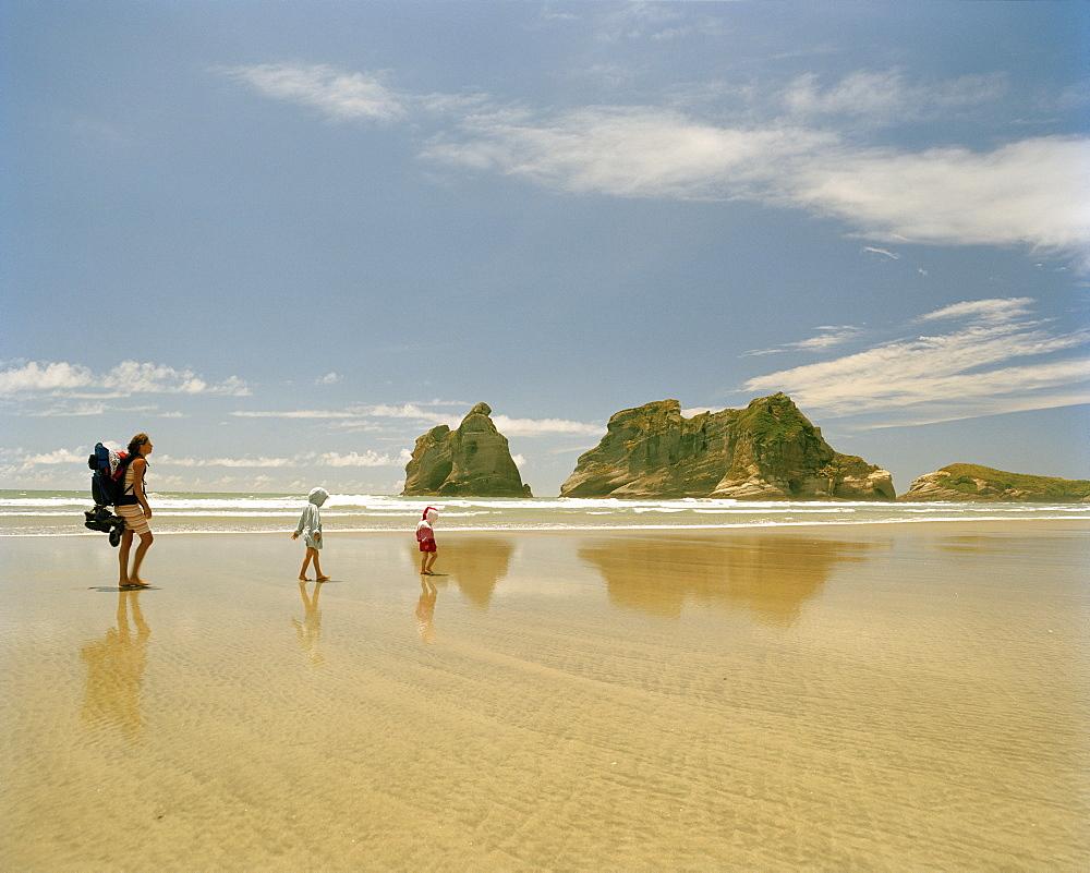 Mother with children hiking through shallow water, Wharariki Beach, northwest coast, South Island, New Zealand