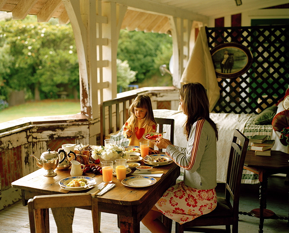 A woman and a girl having breakfast on the balcony, Rowendale Homestead, Okains Bay, Banks Peninsula, South Island, New Zealand