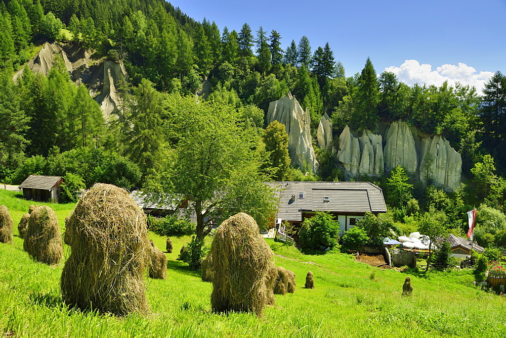 Hay stacks with restaurant and earth pyramids of Terenten in the background, Terenten, Puster valley, South Tyrol, Italy