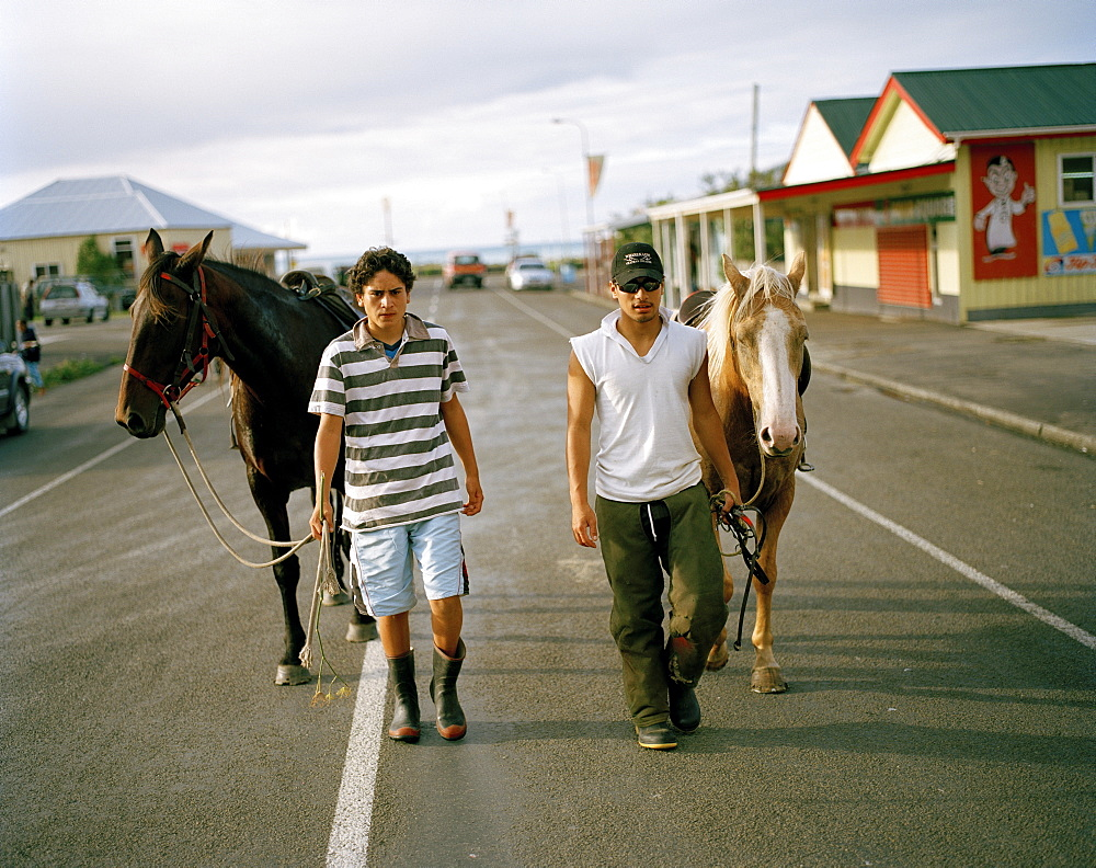 Two young Maori men with horses on the main street of the village Te Araroa, Eastcape, North Island, New Zealand