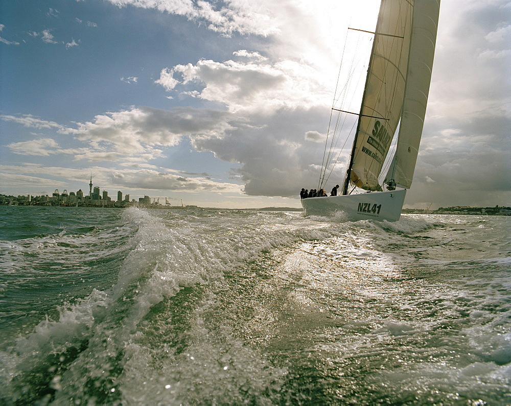 Sailing boat and backwash under clouded sky, Waitemata Harbour, Auckland, North Island, New Zealand