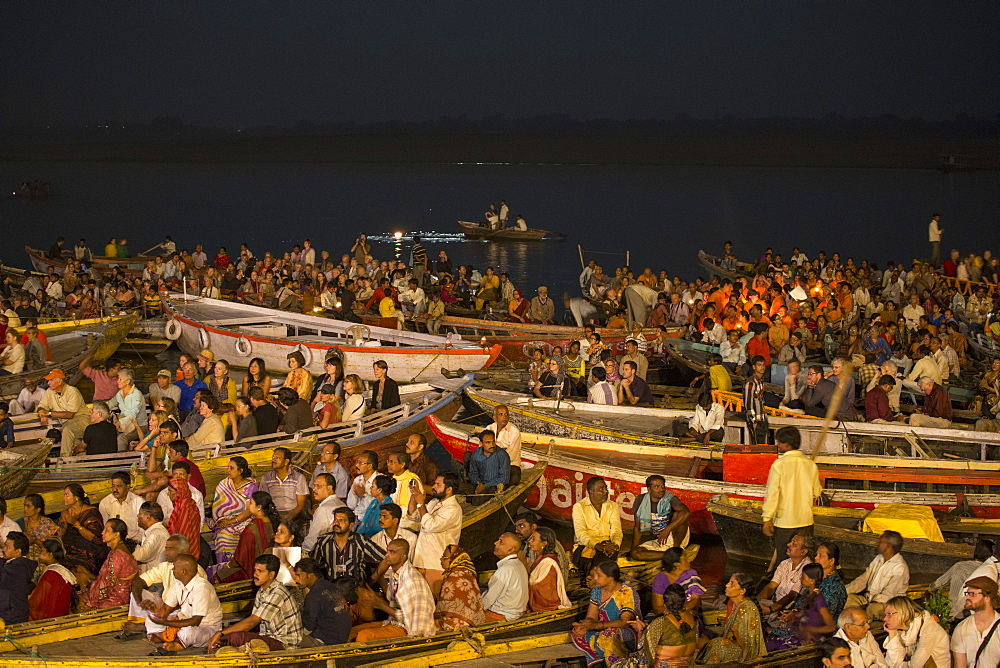 Crowds in boats admire evening Aarti prayer ceremony at Dasaswamedh Ghat alongside Ganges river, Varanasi, Uttar Pradesh, India