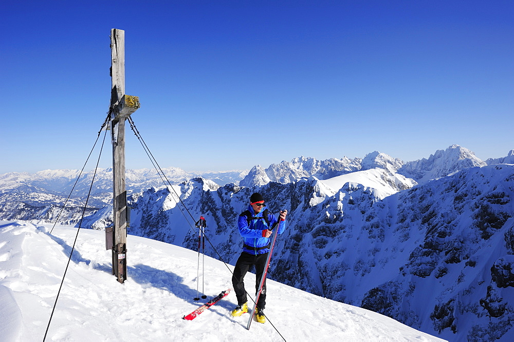 Young man removing skins from backcountry ski, summit of Pyramidenspitze, Kaiser-Express, Zahmer Kaiser, Kaiser mountain range, Tyrol, Austria