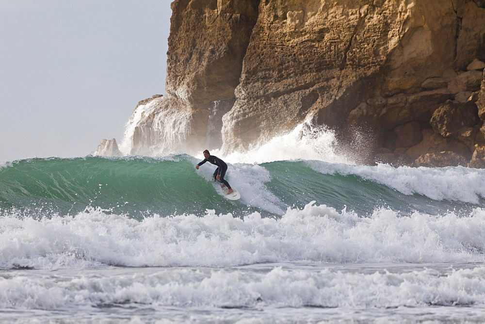 Surfer near cliffs, east coast, Castle Point, North Island, New Zealand - 1113-96066