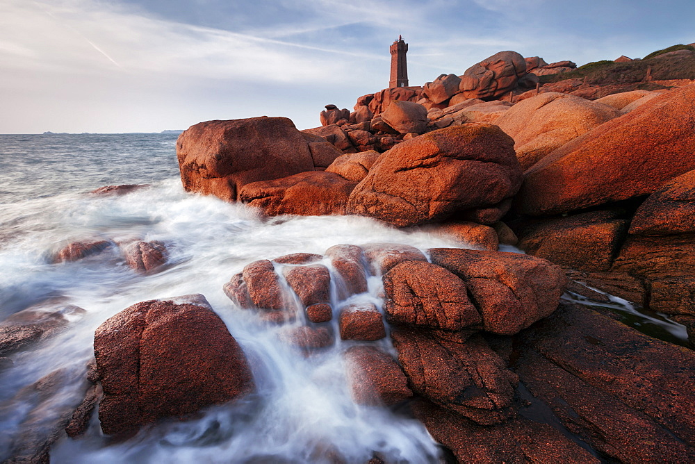 Mean Ruz lighthouse with typical red stones of the Cote de Granit Rose in the morning sun, Brittany, France