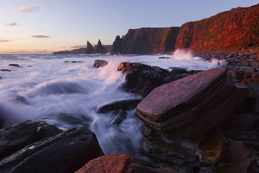 Impressively illuminated red, wild coast of Duncansby Head on the northeastern coast of Scotland with the Duncansby Stacks in the background, United Kingdom