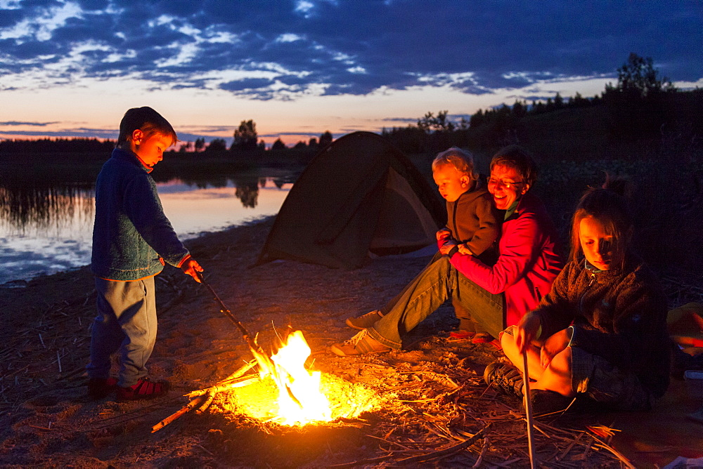 Family at campfire, Werbeliner See, Saxony, Germany
