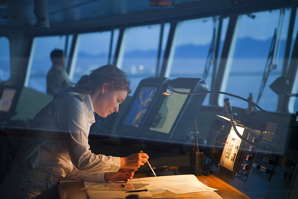 Safety Officer Claudia Kempkes charting course on bridge of cruise ship MS Deutschland (Reederei Peter Deilmann) at dawn, Puerto Vallarta, Jalisco, Mexico
