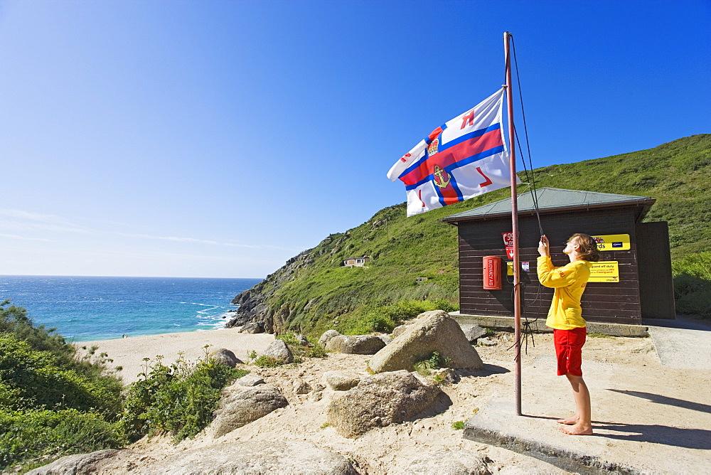 Woman flying a flag, Porthcurno Beach, Penwith peninsula, Cornwall, England, United Kingdom