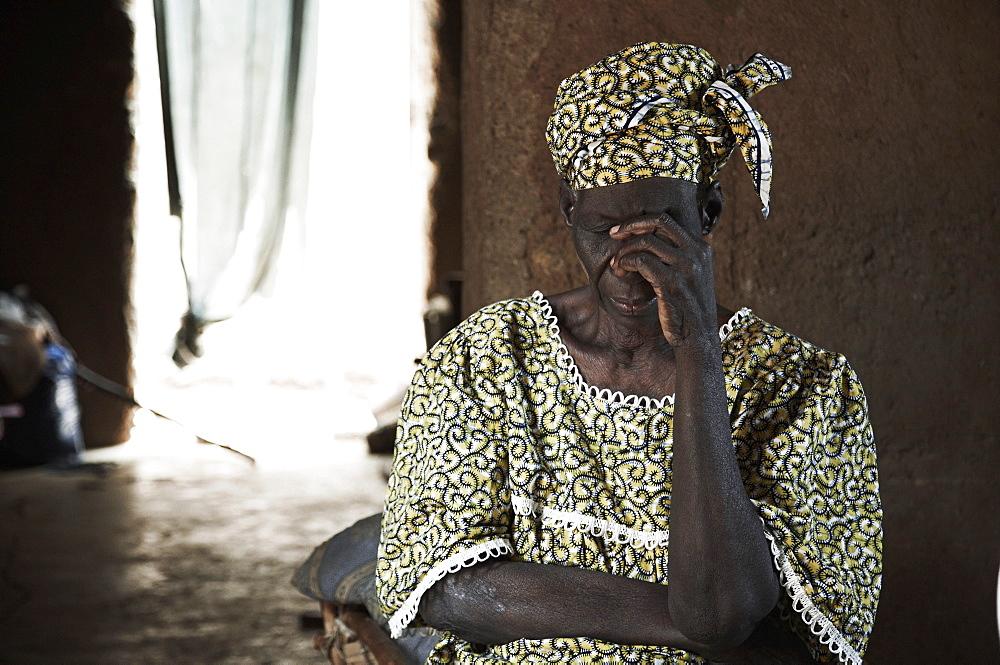 Senior woman inside a mud hut, Yanfolila, Sikasso Region, Mali