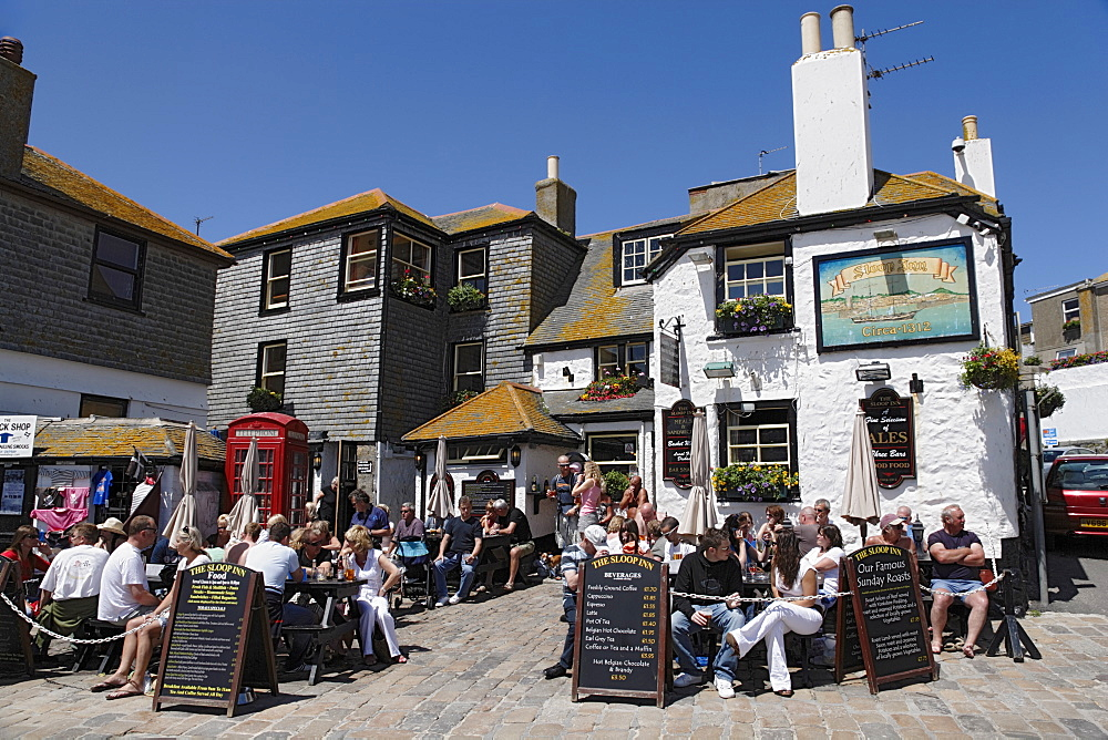 People sitting in front of the Sloop Inn, St. Ives, Cornwall, England, United Kingdom
