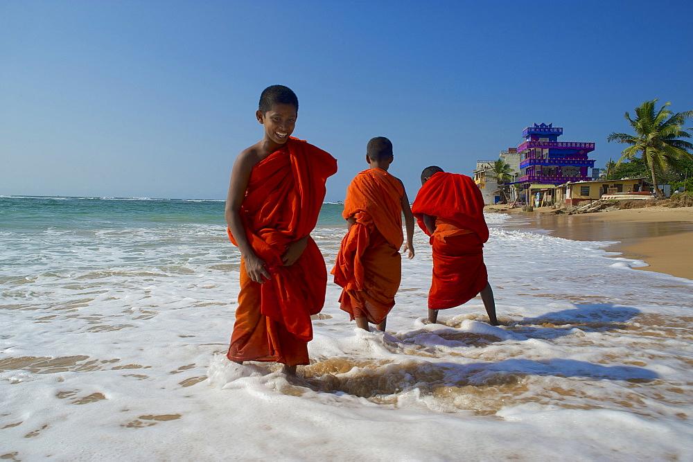 Buddhist novice on the beach at Hikkaduwa, Southwest coast, Sri Lanka, South Asia