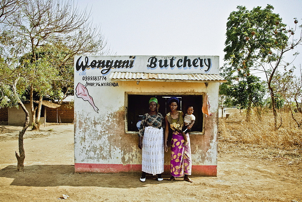 Mother, daughter and granddaughter in front of their family-owned butchers, outside of Lilongwe, Malawi, Africa