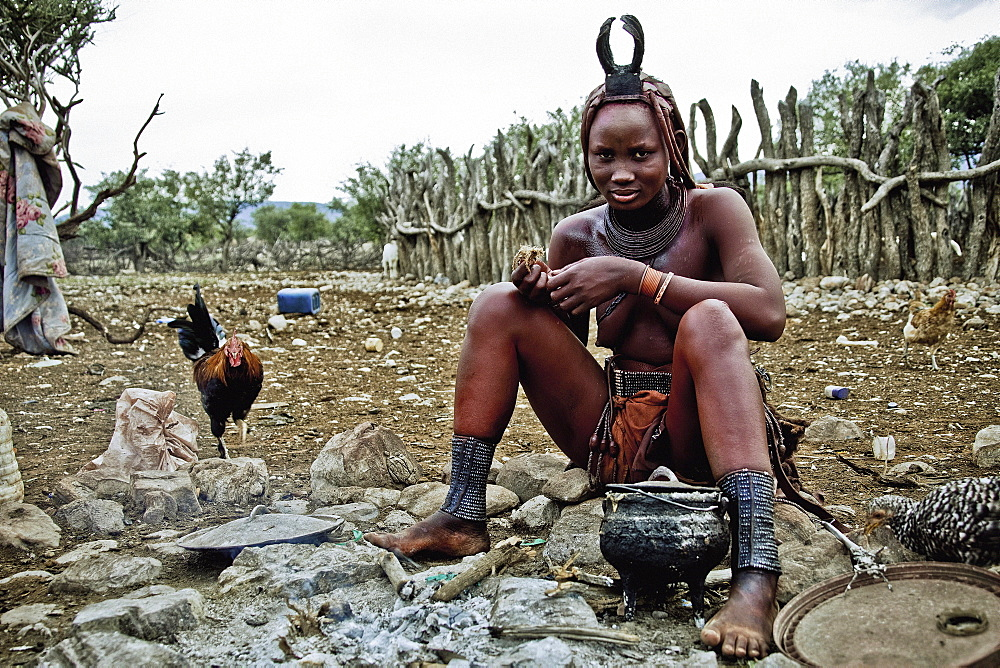Woman of the Himba tribe sitting at the campfire, Kaokoland, Namibia, Africa