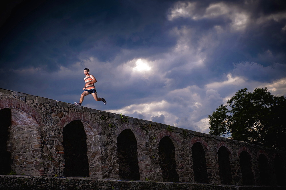 Man running along castle wall, Linz, Upper Austria, Austria