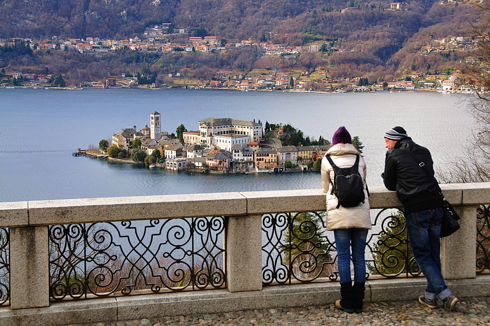 Couple looking towards the Island of San Giulio, Lago d'Orta, Piedmont, Italy