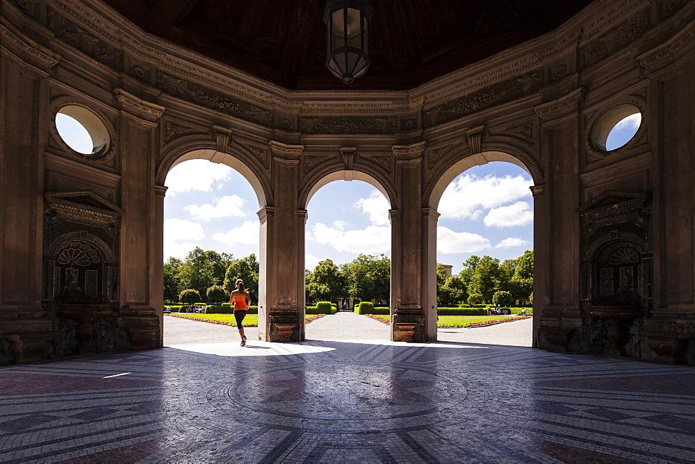 Young woman jogging through Dianatempel, Hofgarten, Munich, Bavaria, Germany