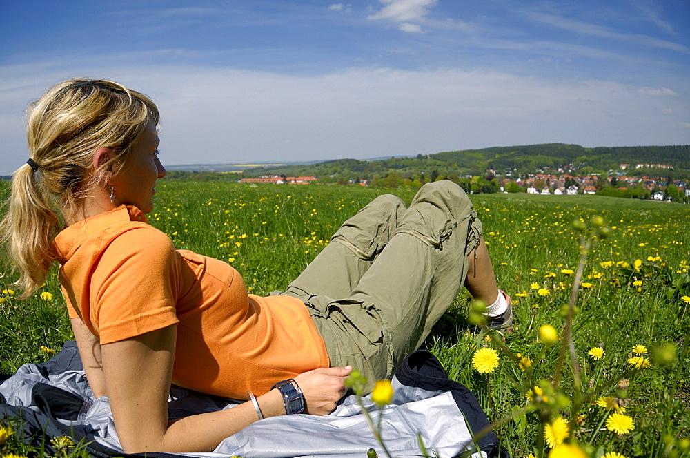 Woman sitting in a meadow, hiking tour near Tabarz, near Eisenach, Thuringia, Germany