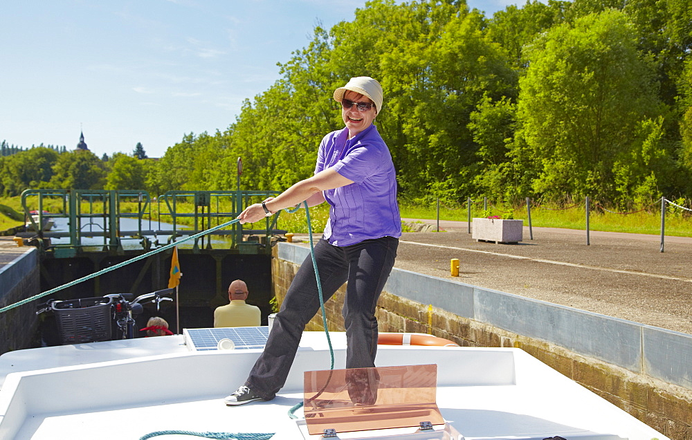 Woman on houseboat on the Canal des Houilleres de la Sarre, Lock 29, Moselle, Region Alsace Lorraine, France, Europe