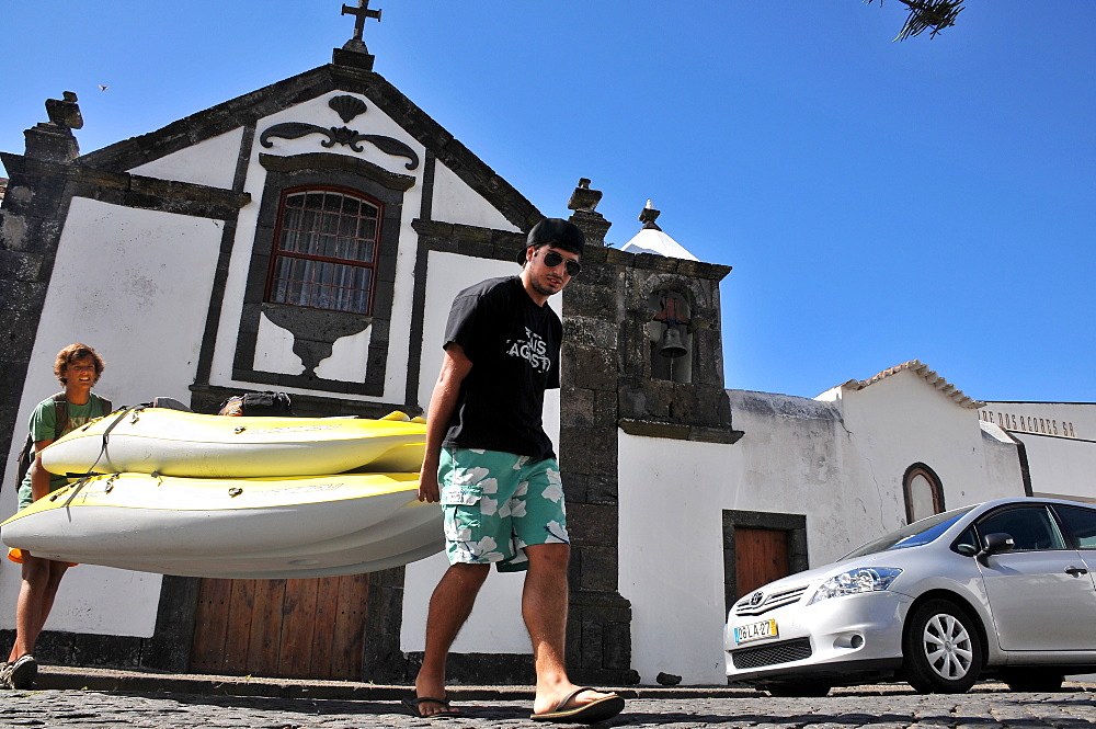 Two teenagers carrying canoes, In Santa Cruz, Island of Graciosa, Azores, Portugal