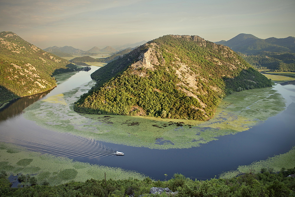 View of the river bend of the Rijeka Crnojevica river with boat, Lake Skadar National Park, Montenegro, Western Balkan, Europe