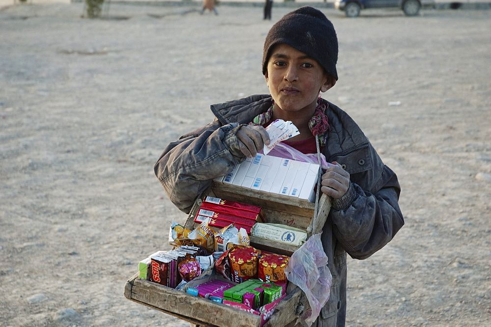Afghan boy selling cigarettes and candy on the Tapa Maranjan Ridge in Kabul,, Afghanistan