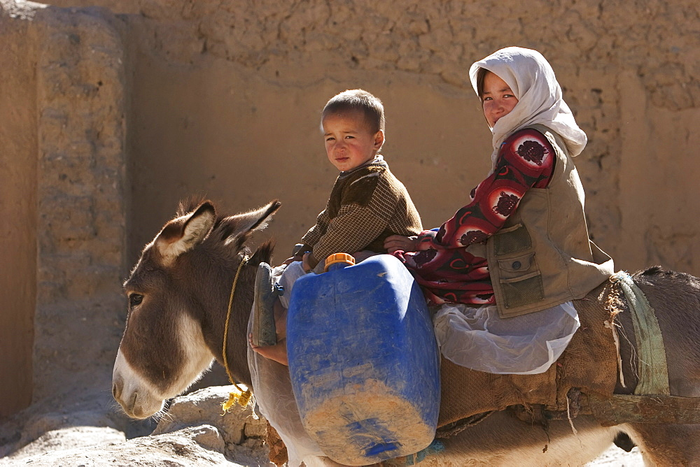 Boy and girl on a donkey in Bamiyan, Bamian Province, Afghanistan