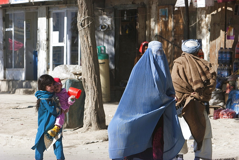 Girl and child follow their mother wearing a burqa on a Kabul street, , Afghanistan