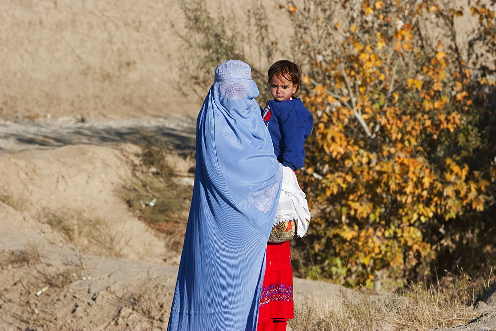 Afghan woman wearing a burqa holding a girl along the Kabul-Charikar Road, Parwan Province, Afghanistan