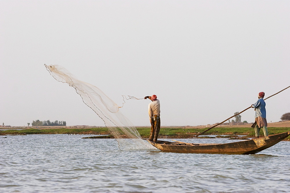 Fisherman throwing a net into the Niger River between Mopti and Lake Débo, Mali