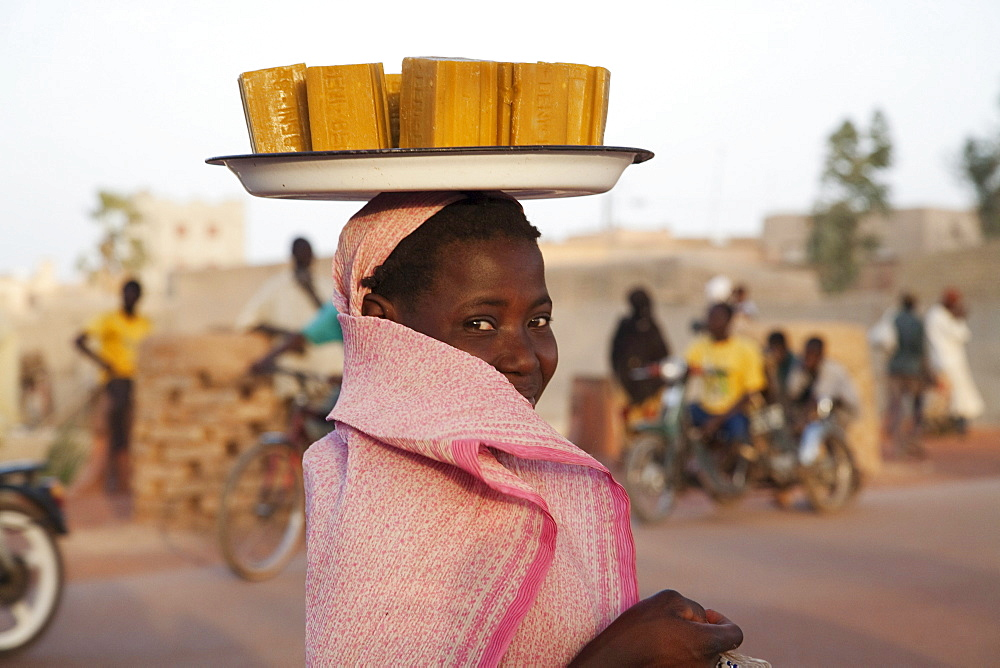 Woman carrying soap bars of her head, Mopti, Mali