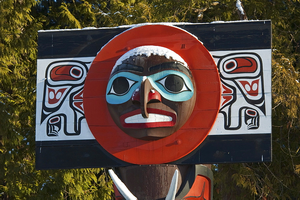 Moon on Chief Skedans Mortuary Pole carved in Haida style by Bill Reid with Werner True covered in snow in Stanley Park, Vancouver, British Columbia, Canada