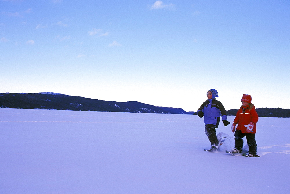 Young Girls Snowshoe across Snow Covered Lake, Northern Ontario